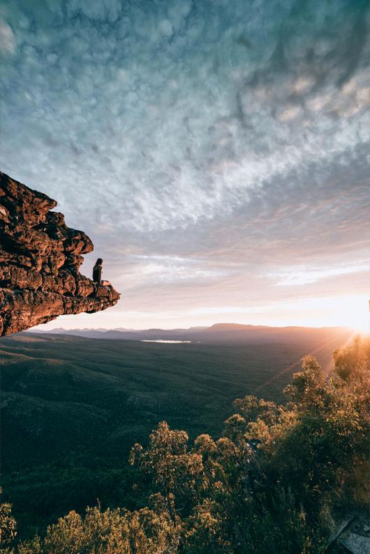 Eine hübsche junge Frau, beim Backpacking in Australien, sitzt auf einen gewaltigen Felsenvorsprung im Grampians National Park und genießt die wunderschöne Natur und einen fantastischen Sonnenuntergang. Sie trägt eine robuste Shorts und ein luftiges Tank-Top. │ Backpacking im Grampians National Park, Australien │ Die besten Shorts zum Reisen und für Outdoor Abenteuer │ Standort: Grampians National Park, Victoria, Australien, Ozeanien │ Abenteuer Reiseblog │ Reise- und Outdoor Ausrüstung │ Shorts