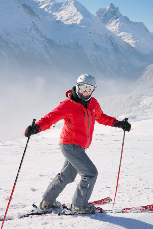 Eine hübsche junge Skifahrerin hat richtig Spaß beim Skifahren und schenkt der Kamera ein wundervolles freudiges Lächeln – Ihre atmungsaktive Softshelljacke und Softshellhose sind ideal zum Skifahren und schützen sie perfekt vor der Nässe des Schnees │ Skifahren │ Die besten Softshelljacken und Softshellhosen zum Reisen und für Outdoor Abenteuer │ Abenteuer Reiseblog │ Reise- und Outdoor Ausrüstung │ Softshell Jacken und Hosen