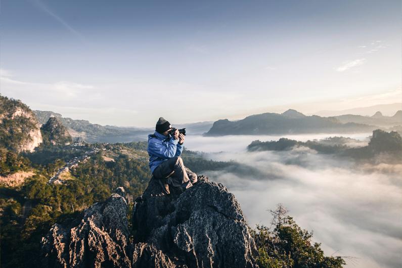Ein Wanderer, beim Wandern in Thailand, sitzt in Baan Ja Bo auf einem Berggipfel und fotografiert mit seiner Kamera die wundervolle Landschaft – – Seine Softshelljacke und Softshellhose schützen in beim Wandern und Klettern vor spitzen Felsen und Sträuchern und sind zudem für sportlichen Aktivitäten super atmungsaktiv │ Wandern in Baan Ja Bo, Thailand │ Die besten Softshelljacken und Softshellhosen zum Reisen und für Outdoor Abenteuer │ Standort: Baan Ja Bo, Mae Hong Son, Thailand, Südostasien, Asien │ Abenteuer Reiseblog │ Reise- und Outdoor Ausrüstung │ Softshell Jacken und Hosen