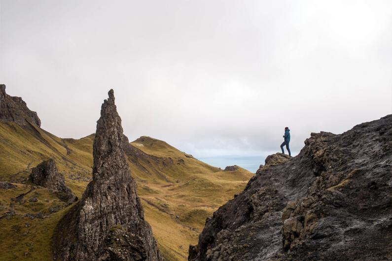 Ein Wanderer, beim Wandern auf der schottischen Insel Skye, steht vor der imposanten Old Man of Storr Felsnadel und genießt die fantastische Landschaft – Er trägt eine atmungsaktive Softshelljacke und Softshellhose und ist damit super vor leichter Nässe und spitzen Sträuchern und Felsen geschützt │ Wandern zur Old Man of Storr auf Skye │ Die besten Softshelljacken und Softshellhosen zum Reisen und für Outdoor Abenteuer │ Standort: Old Man of Storr, Portree, Skye, Schottland, Großbritannien, Europa │ Abenteuer Reiseblog │ Reise- und Outdoor Ausrüstung │ Softshell Jacken und Hosen
