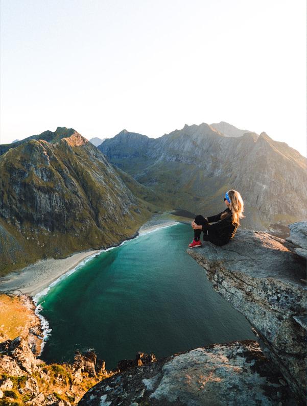 Eine hübsche junge Frau, bei einer Traumreise auf die Lofoten in Norwegen, sitzt am Rand eines atemberaubend schönen und hohen Felsenvorsprungs und genießt die wundervolle Aussicht auf die Berge und einen süßen kleinen Strand. Sie trägt bei Wandern eine sportliche Leggings │ Traumreise auf die Lofoten in Norwegen │ Die besten Sporthosen, Badehosen und Bikinis zum Reisen und für Outdoor Abenteuer │ Standort: Lofoten, Norwegen, Skandinavien, Europa │ Abenteuer Reiseblog │ Reise- und Outdoor Ausrüstung │ Sporthosen und Badebekleidung