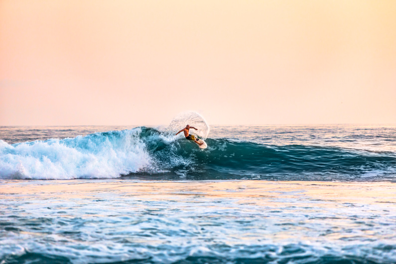 Ein extrem guter Surfer, nur mit einer Boardshorts bekleidet, surft eine hohe Welle im Meer und genießt das wunderschöne warme Wetter und einen wundervollen Sonnenuntergang │ Surfen/Wellenreiten │ Die besten Sporthosen, Badehosen und Bikinis zum Reisen und für Outdoor Abenteuer │ Abenteuer Reiseblog │ Reise- und Outdoor Ausrüstung │ Sporthosen und Badebekleidung