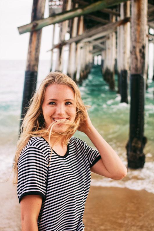 Eine hübsche junge Frau, bei einer Traumreise nach Kalifornien, steht am Strand unter einem Pier in Huntington Beach und hat Spaß mit ihren Freunden – Sie trägt ein schickes blau-weiß gestreiftes T-Shirt │ Traumurlaub in Huntington Beach, Kalifornien │ Die besten T-Shirts zum Reisen und für Outdoor Abenteuer │ Standort: Huntington Beach, Kalifornien, USA, Nordamerika, Amerika │ Abenteuer Reiseblog │ Reise- und Outdoor Ausrüstung │ T-Shirts