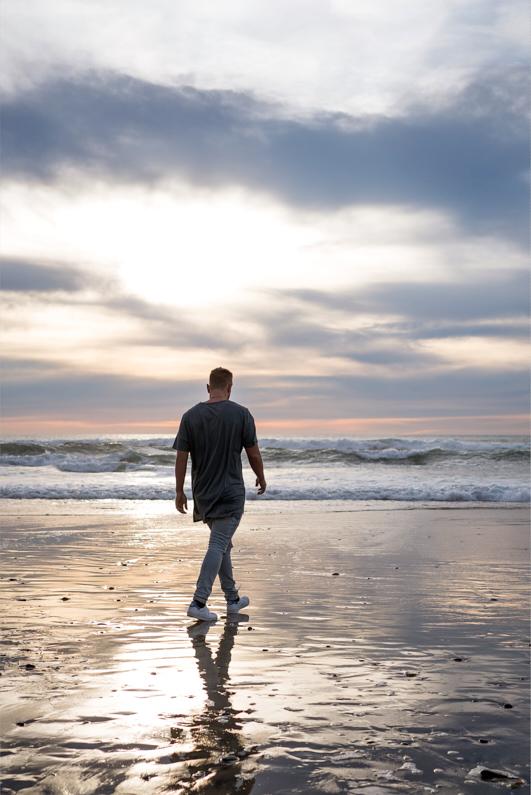 Ein hübscher junger Mann, bei einer Traumreise nach Kalifornien, geht am Strand von Encinitas spazieren und genießt einen wunderschönen Sonnenuntergang – Er trägt ein schickes graues T-Shirt, eine graue Hose und weiße Turnschuhe │ Traumurlaub in Encinitas, Kalifornien │ Die besten T-Shirts zum Reisen und für Outdoor Abenteuer │ Standort: Encinitas, Kalifornien, USA, Nordamerika, Amerika │ Abenteuer Reiseblog │ Reise- und Outdoor Ausrüstung │ T-Shirts