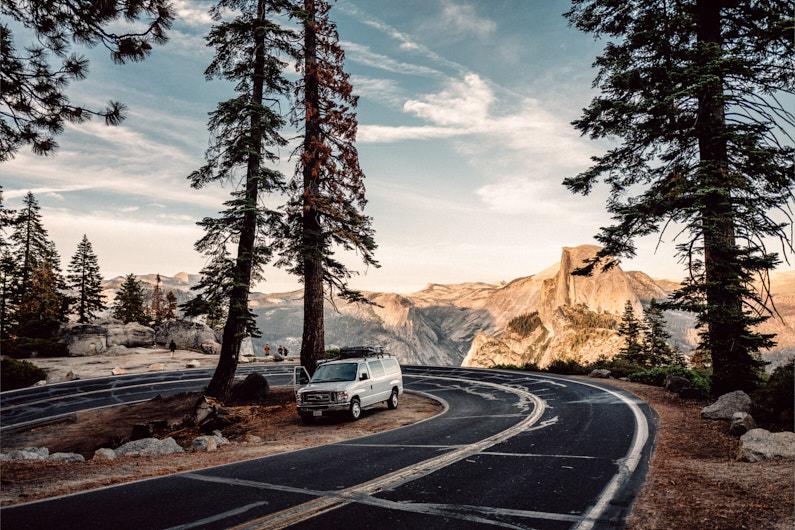 Ein Wohnwagen steht am Straßenrand einer super eng geschlungenen Straße in den Bergen, auf dem man einen wundervollen Ausblick auf den 2693m hohen Half Dome Berg im kalifornischen Yosemite Nationalpark hat │ Roadtrip/Rundfahrt durch den Yosemite Nationalpark in Kalifornien │ Wertvolle Informationen für Roadtrips │ Standort: Yosemite Nationalpark, Kalifornien, USA, Nordamerika, Amerika │ Abenteuer Reiseblog │ Reiseanleitung │ Tipps und Tricks für Selbstfahrer auf Reisen