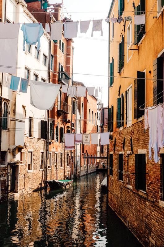 Blick auf einen Kanal in Venedig, bei einer Traumreise nach Italien, in dem frisch gewaschene Wäsche auf zwischen den Häusern gespannte Wäscheleinen aufgehängt ist │ Wäsche waschen in Venedig, Italien │ Die besten Tipps und Tricks zum Wäsche waschen auf Reisen und Outdoor Abenteuern │ Standort: Venedig, Venetien, Italien, Europa │ Abenteuer Reiseblog │ Reise- und Outdoor Ausrüstung │ Wäsche waschen auf Reisen