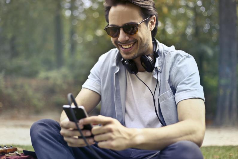 Ein junger hübscher Mann sitzt während einer Reise ins Ausland in einem Park und genießt es mit seinen Freunden Zuhause zu telefonieren │ Telefonieren, Internet surfen und texten │ Im Ausland günstig telefonieren und im Internet surfen │ Abenteuer Reiseblog │ Reiseanleitung │ Weltweit günstig telefonieren und im Internet surfen